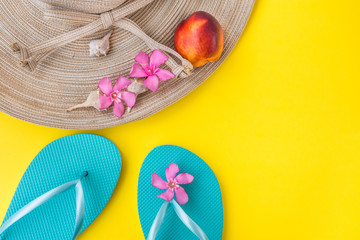 Women's straw hat, pink tropical flowers, blue slippers, sea shells, nectarine on yellow background, beach vacation, seaside, fashion, top view