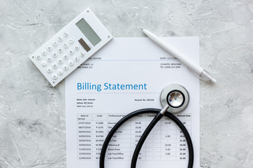 stethoscope, billing statement for doctor's work in medical center stone background top view