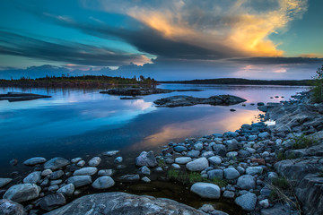 Fotobehang Rivier There are many stones near the shore. Reflection of the sky in the water. Northern landscape. Wild nature of the north. Karelia. Ladoga lake.