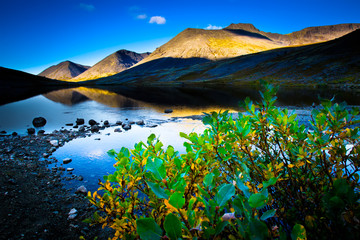Reflection of mountains in the water. Mountain Lake. Evening in the mountains.