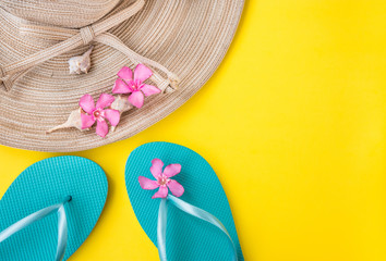 Women's straw hat, pink tropical flowers, blue slippers, sea shells, on yellow background, beach vacation, seaside, fashion, top view