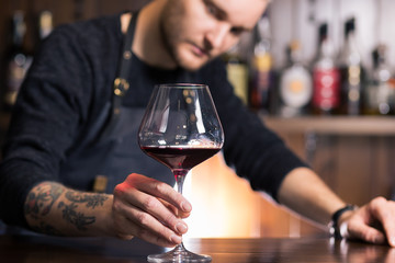 Skilled sommelier pouring wine. Man in black suit and white shirt looks concentrated: he's evaluating quality of wine being pouring. Process of tasting wine captured in photo.