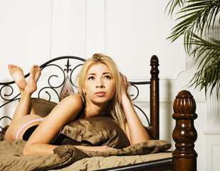 young pretty blond real woman in bed covered white sheets smiling cheerful sexy look close up, happy morning concept, lifestyle people
