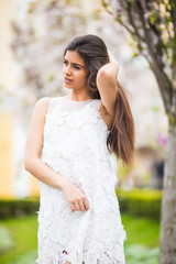Beautiful attractive girl in dress posing in city park. Outdoor fashion portrait of woman posing on the street