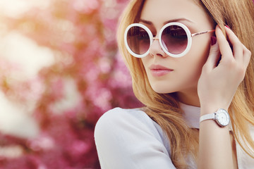 Outdoor close up portrait of young beautiful fashionable girl posing in street. Model wearing stylish white round sunglasses, wrist, hand watch. Female fashion concept. Copy, empty space for text