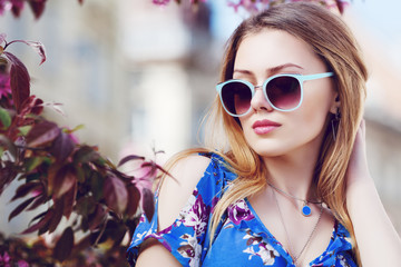Outdoor close up portrait of young beautiful fashionable girl posing in street. Model wearing stylish sunglasses, blue off shoulders dress. Female fashion concept. Copy, empty space for text