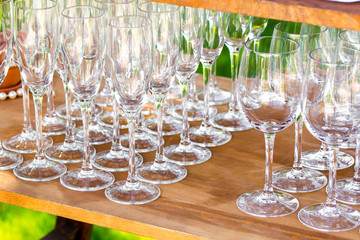Champagne and wine glasses in a row preapred for outdoor party .