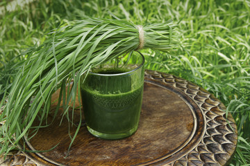 Glass of wheatgrass juice on a brown wooden table