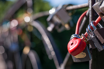 The lock is red in the form of a heart, hanging next to other locks. Horizontal frame
