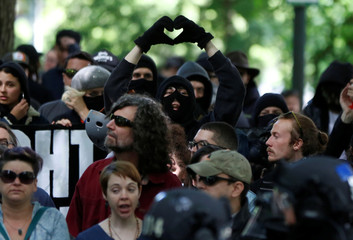An anti-facist protester makes the heart symbol during competing demonstrations in Portland, Oregon, U.S.