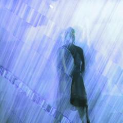 Silhouette einer Frau in einem Kleid mit Bewegungsunschärfe und verwischtem Hintergrund in blau