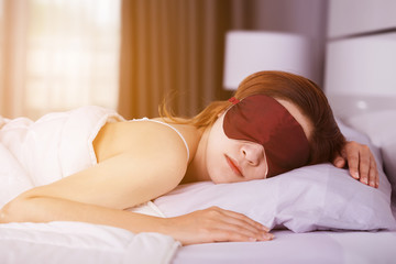 Woman sleeping on bed with eye mask in bedroom with soft light