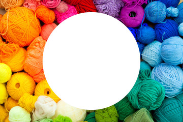 Colorful yarn stacked in a series of colors. Background brown kraft paper. Balls and skeins of colored yarn for knitting. The color wheel of the yarn.