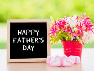 Father's Day concept. Poster mock up template with Happy father's day text and flower bouquet, marshmallow in the shape of heart and books over green background