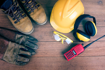 Top view of Standard construction safety equipment on wood background