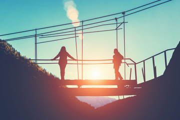 Silhouettes of two women on a bridge at sunset