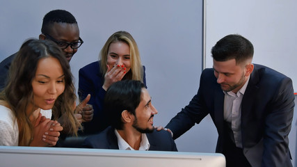 Group of multiracial business team shoked with result, surprised, smiling and looking at laptop computer