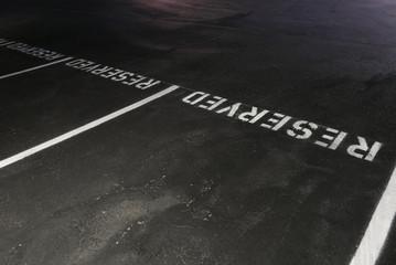 Parkplatz mit der englischen Aufschrift RESERVED auf der Bordsteinkante