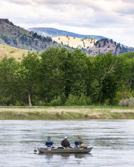 Three fishermen in a rowboat in the Missouri River, Montana, fishing with their backs to the camera. Vegetation and foothills are in the background and cloudy sky above.