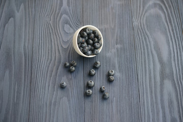 Blueberries in a white bowl on a wooden background
