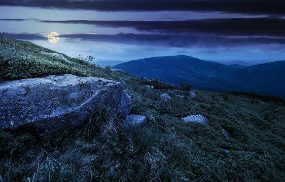 boulder on the grassy hillside at night