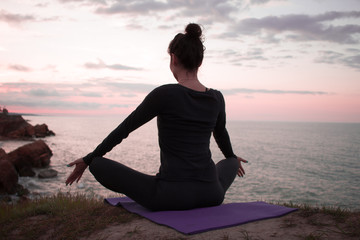 Fit woman doing stretching exercise outdoor.Silhouette of woman in yoga poses