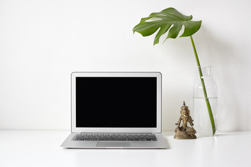 Front view of a laptop with blank copy space screen, Monstera branch in vases, statue of Green Tara. Minimalistic desktop of manager in yoga studio. White backgroud, mock up computer