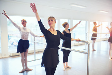Mature women standing and dancing ballet with hands up