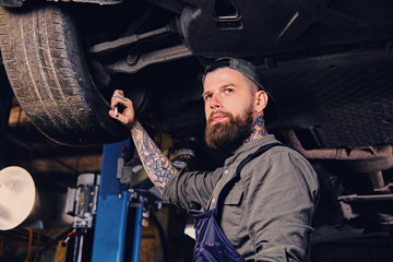 Mechanic balancing car's wheel in a workshop.