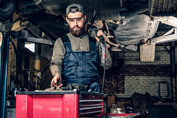 Mechanic holds angle grinder on a shoulder.