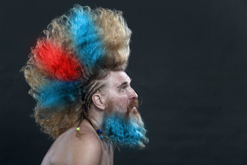 adult man with a beard and a high red and blue mohawk