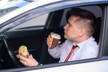 Businessman eating a burger and drink coffee in the car.