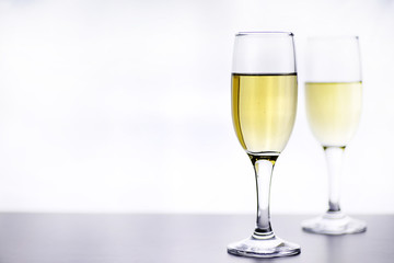 glass of white wine on a table on white background isolate