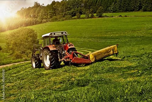 Prächtig Traktor mit Mähwerk bei der Heuernte in der Abendsonne