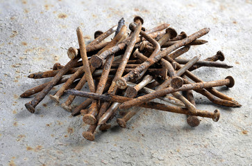 A pile of old nails on a metal background