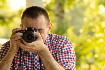 Photographer takes pictures against the background of greenery. Front view