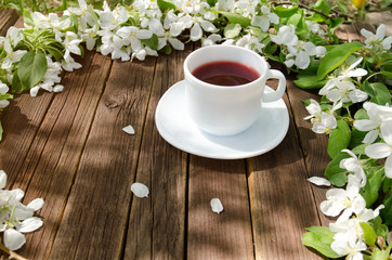 White mug of tea on a wooden table, apple blossoms in the background. Sunny, side view