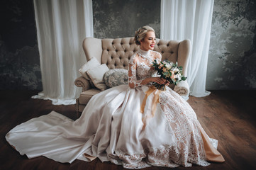 Beautiful bride in wedding lace dress with wedding bouquet with orange and white flowers. Studio, gray background, modern, sofa.