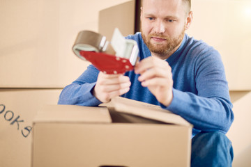 Young Caucasian man using duct tape for packing stuff in box