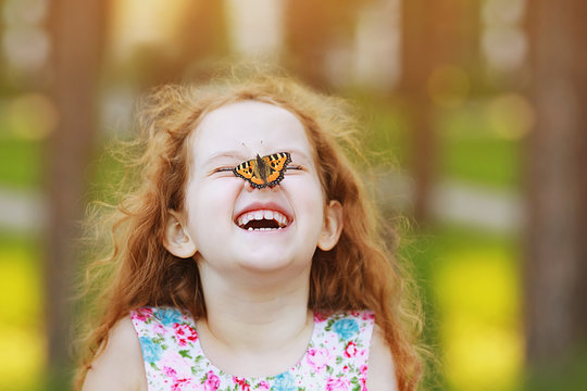 Laughing funny girl with a butterfly on his nose.