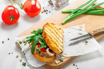 Grilled sandwich with tuna salad, tomato, onion and arugula on a white wooden table. Diet healthy finger food made of toasts, vegetables and fish.