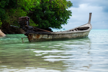longtail boat of fisherman parking on shallow sea. have sea and mountain are background. this image for nature,seascape,travel and transport concept
