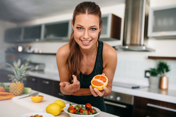 Young woman pointing towards a cut orange in kitchen.