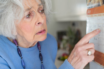 Confused Senior Woan With Dementia Looking At Wall Calendar