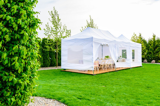 Party tent - white garden party or wedding entertainment tent in modern garden