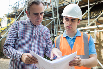 Customer On Site Discussing Plans With Builder