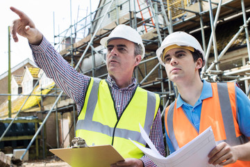 Architect On Site Discussing Plans With Builder