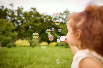 Child is playing with soap bubbles in the park. Background with soap bubbles.