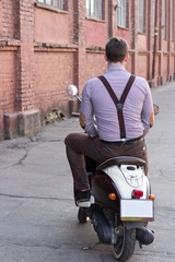 old fashioned guy with a retro motor scooter