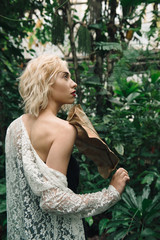 Fashion portrait of beautiful young woman in tropical forest